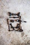 工具和零件安排了以在水泥的一张兴高采烈的面孔的形式 库存图片