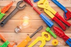 工具和仪器戏弄与在木纹理的电灯泡 库存照片