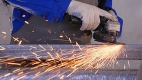 工匠与盘研磨机的锯切金属在车间 与火花飞行的研的金属 研电的轮子  免版税图库摄影