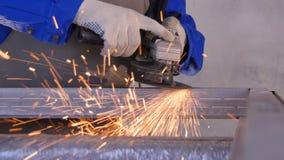 工匠与盘研磨机的锯切金属在车间 与火花飞行的研的金属 研电的轮子  免版税库存照片