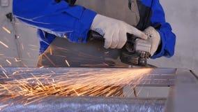 工匠与盘研磨机的锯切金属在车间 与火花飞行的研的金属 研电的轮子  库存照片