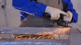 工匠与盘研磨机的锯切金属在车间 与火花飞行的研的金属 研电的轮子  免版税库存图片