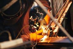 工匠修理有角度研磨机的一辆汽车 免版税库存照片