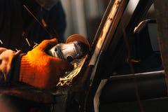 工匠修理有角度研磨机的一辆汽车 库存图片