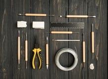 工匠工作场所,为雕刻准备从聚合物黏土 葡萄酒与造型工具的工作表 平的位置,顶视图 免版税图库摄影