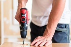 工匠或DIY人与机械钻一起使用 免版税库存照片
