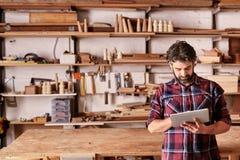 工匠木匠在他的使用数字式片剂的木制品演播室 免版税库存照片