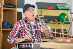 工匠焊接的铜管子 免版税库存照片