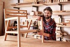 工匠铺沙一把椅子的家具设计师在他的车间 免版税库存图片