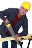 工匠锯切木头 图库摄影
