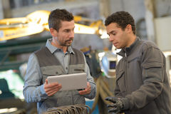 工厂劳工谈论与数字式片剂在仓库 库存照片