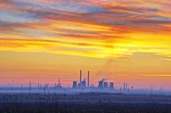 工厂在日落多云天空下 免版税库存图片