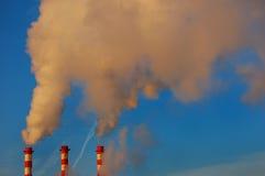 工厂用管道输送在蓝天的烟 免版税库存照片