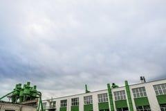 工厂的看法 在天空蔚蓝背景的绿色大厦 免版税库存照片