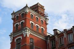工厂的老,但是被重建的工厂厂房从红砖的与白色修剪,在看法之外,反对蓝天 免版税库存照片