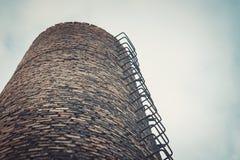 工厂砖烟囱特写镜头  由工业排放的大气污染 库存照片
