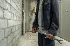 工厂站立的金属板钳的技工在工厂的背景 库存照片