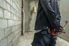 工厂站立的金属板钳的技工在工厂的背景 免版税库存图片