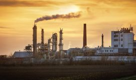 工厂管子污染空气,从烟囱的烟反对太阳, env 免版税库存图片