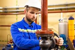 工厂设备的工作者 在锅炉系统的技术员操作员转动的闸式阀 人在盔甲和工作服服务精炼厂 库存图片
