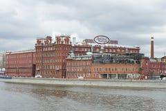 工厂`红色10月`,多云4月天的大厦 莫斯科 免版税图库摄影
