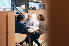 工友一起谈事务在一个现代办公室 免版税库存图片
