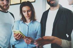 工友业务会议概念 举行流动智能手机手和讨论新闻与她的同事的少妇 免版税库存照片