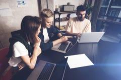 工友合作在工作 小组在创造性的办公室的时髦便衣的年轻商人 免版税库存照片