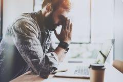 工友运作的过程在晴朗的办公室 做停留的疲乏的年轻有胡子的人在坚苦工作天以后 水平 蠢材 免版税库存照片