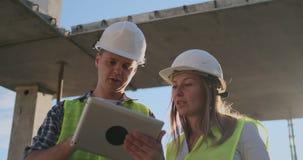 工地工作队或建筑师和建造者或者工作者有盔甲的谈论在绞刑台建筑计划或 股票视频
