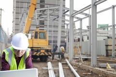 工头使用膝上型计算机的建造场所 免版税库存照片