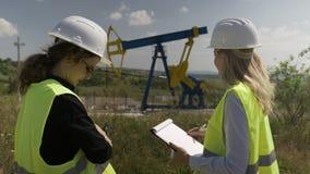 工程学使用数字式片剂和剪贴板的专家工友谈论关于油田产业发展战略- 股票录像