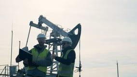 工程师与膝上型计算机一起使用在油田的井架附近 油萃取产业概念 股票录像