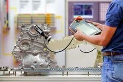 工程师为控制使用无线遥控机器人为工作汽车的扫描零件通过传送带 免版税库存图片