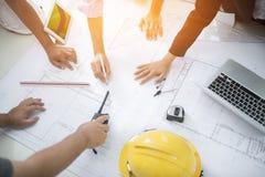 工程师会议的图象建筑项目的 工作与伙伴和设计在工作场所葡萄酒的工具定调子 图库摄影