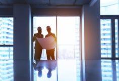 工程师和商人与计划在空的办公室 库存图片
