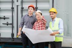 工程师和建筑在手边合作佩带的安全帽和图纸 免版税库存图片