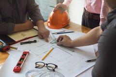 工程师和建筑师概念、工程师建筑师和不动产房地产经纪商办公室队与图纸一起使用 免版税库存图片