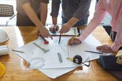 工程师和建筑师概念、工程师建筑师和不动产房地产经纪商办公室队与图纸一起使用 库存图片