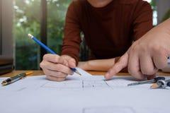 工程师和建筑师概念,工程师建筑师事务所队与图纸一起使用 免版税库存照片