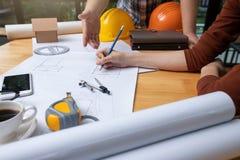 工程师和建筑师概念,工程师建筑师事务所队与图纸一起使用 免版税图库摄影