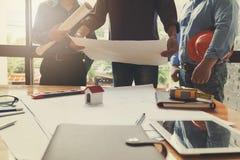 工程师和建筑师概念,工程师建筑师事务所队和谈论与图纸和房子模型一起使用 免版税图库摄影