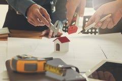 工程师和建筑师概念,工程师建筑师事务所队和谈论与图纸和房子模型一起使用 库存照片