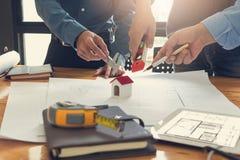 工程师和建筑师概念,工程师建筑师事务所队和谈论房子计划与图纸和房子方式一起使用 免版税库存照片