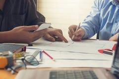工程师和建筑师概念,工程师建筑师事务所队和谈论房子计划与图纸和房子模型一起使用, 免版税库存图片