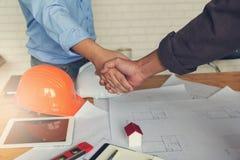 工程师和建筑师概念,工程师运作建筑师事务所的队震动有图纸的手和在办公室des的房子模型 免版税库存图片