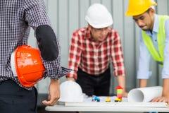 工程师和建筑通过检查建筑进展合作佩带的安全帽和工作图纸的 免版税库存照片