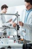 工程师在使用3D打印机的实验室 免版税图库摄影