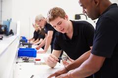 工程师在有学徒的工厂检查组分质量 库存图片