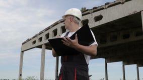 工程师在未完成的大厦附近写 股票录像